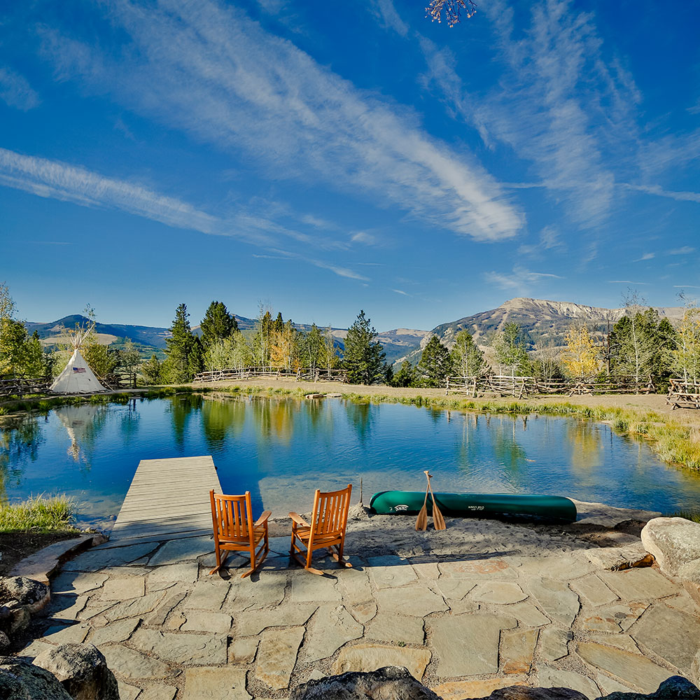Beautiful image of 2 chairs sitting on landscaped rocks overlooking a small private pond
