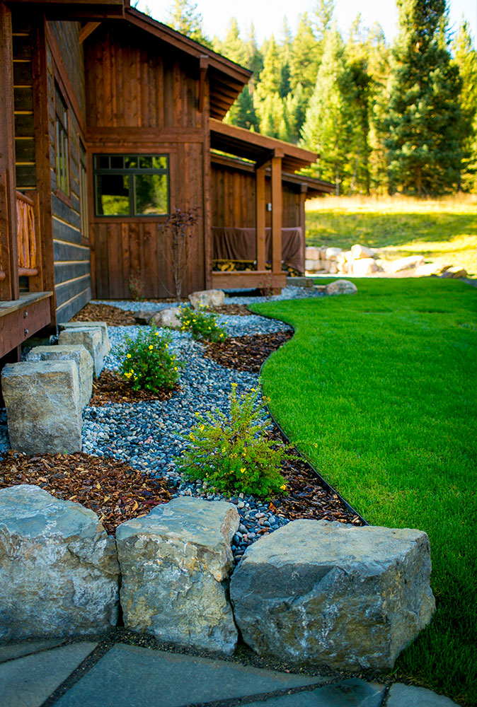 Image of green grass and stone landscaping next to a house