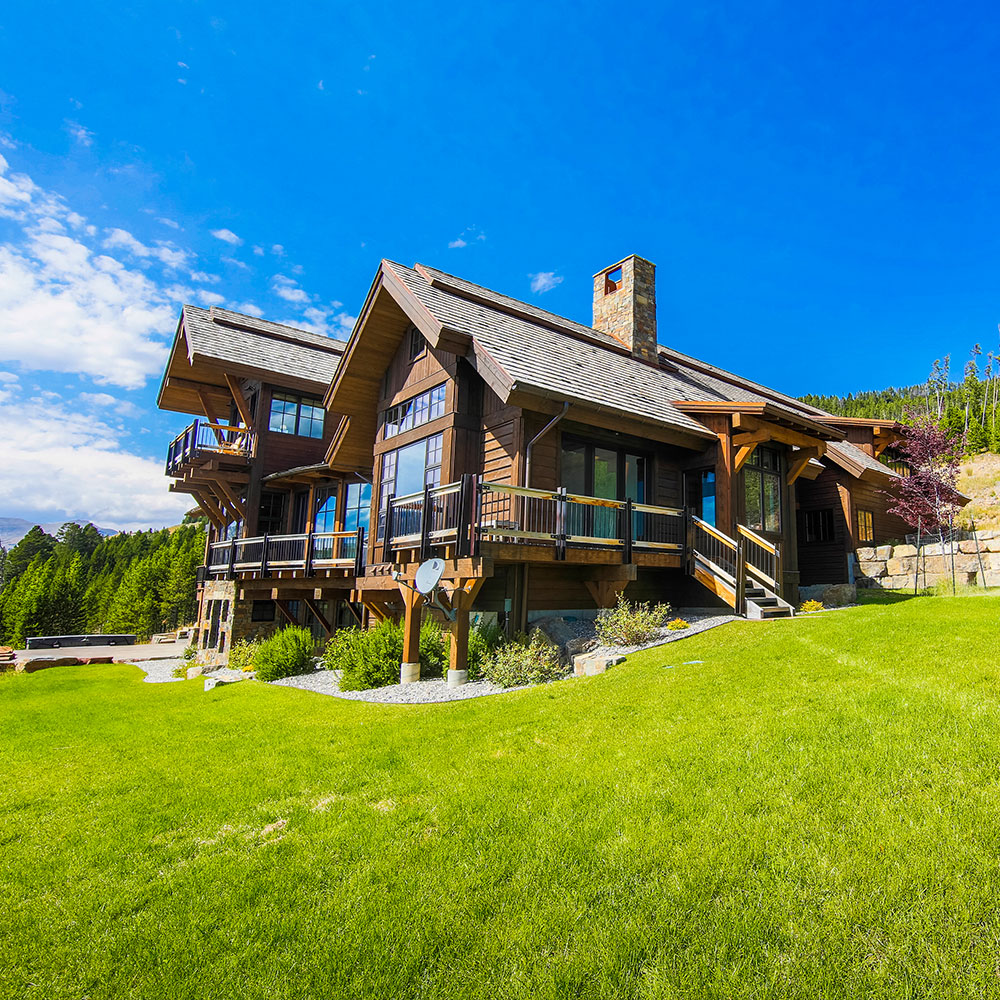 Beautiful home in Big Sky Montana with a large green grassy lawn