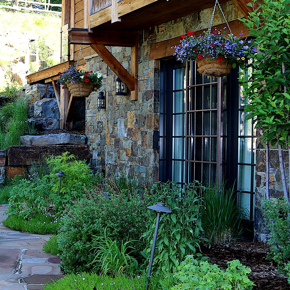 Side of a house with hanging baskets and beautiful green landscaping along the sides