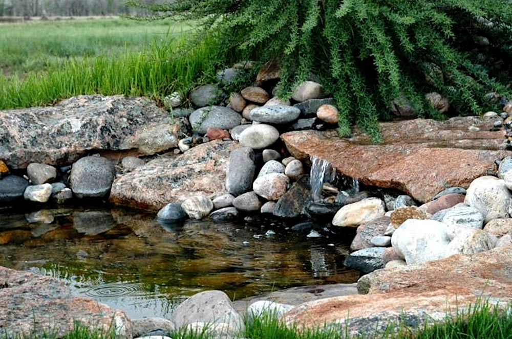 Small pond with a water feature made out of stone