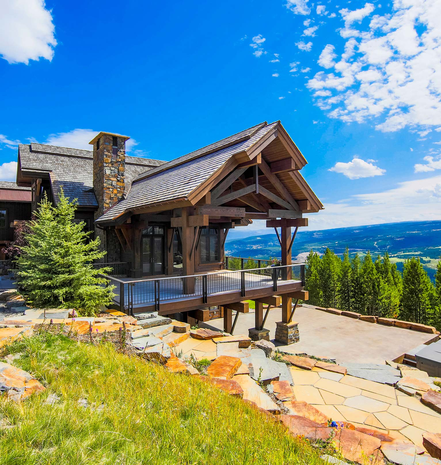Beautiful home overlooking the valley below, with lots of stone paver landscaping leading up to the front door